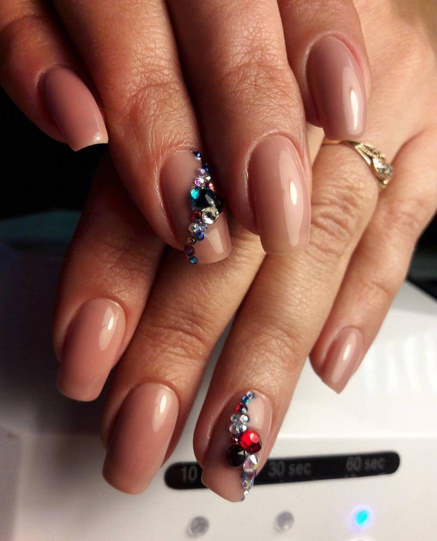 Длинные бежевые ногти с разноцветными камнями